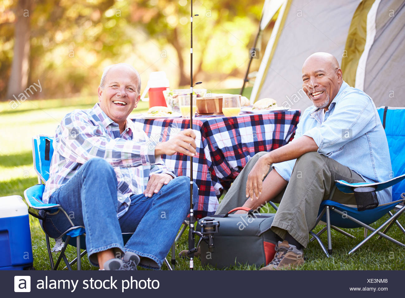 Two Senior Men On Camping Holiday With Fishing Rod - Stock Image