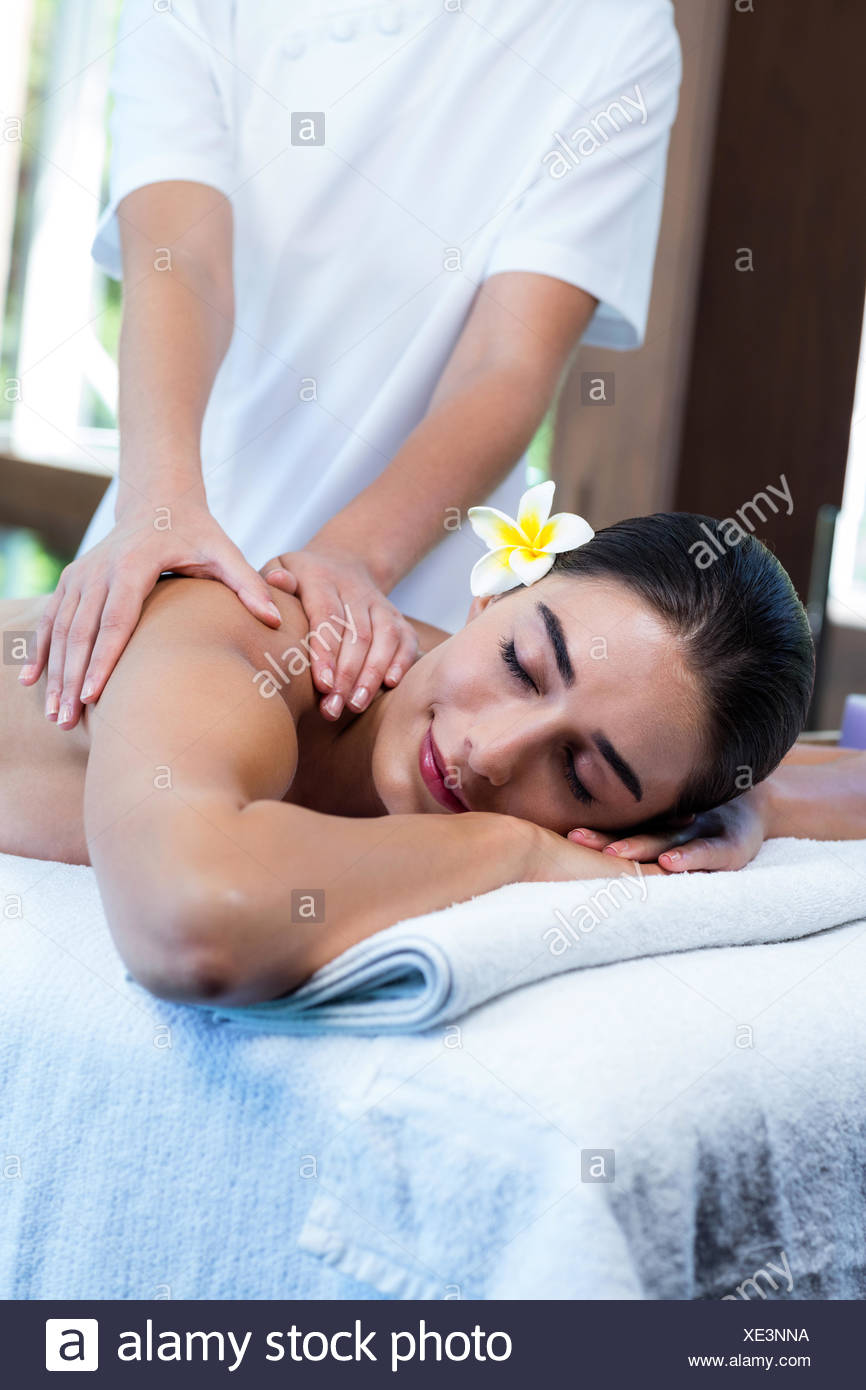 Masseuse giving massage to relax woman Stock Photo