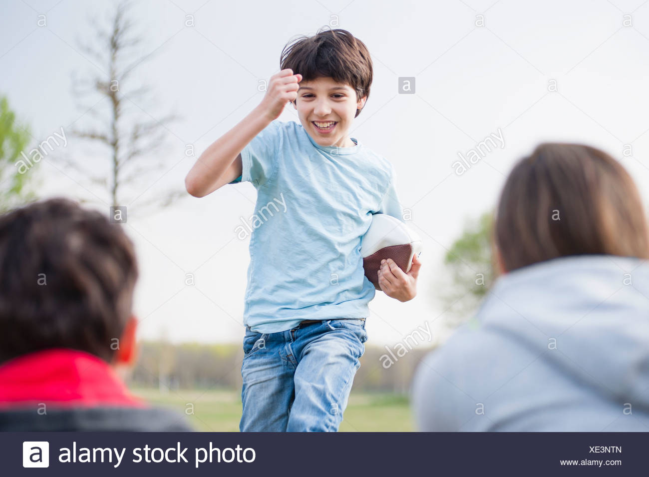 Parents watching son run with rugby ball in park Stock Photo