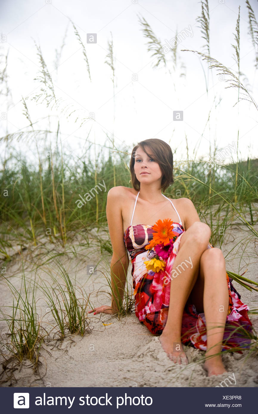 Young woman in sundress sitting in sand dunes on beach - Stock Image