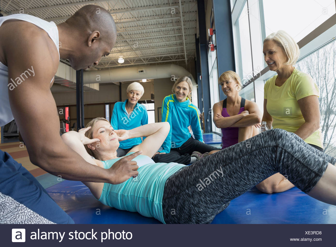 Personal trainer guiding woman甄s sit-ups at gym - Stock Image