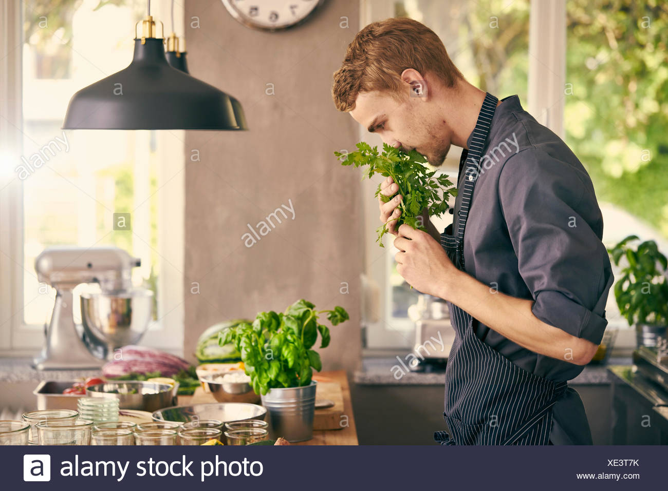 Chef smelling fresh herbs - Stock Image