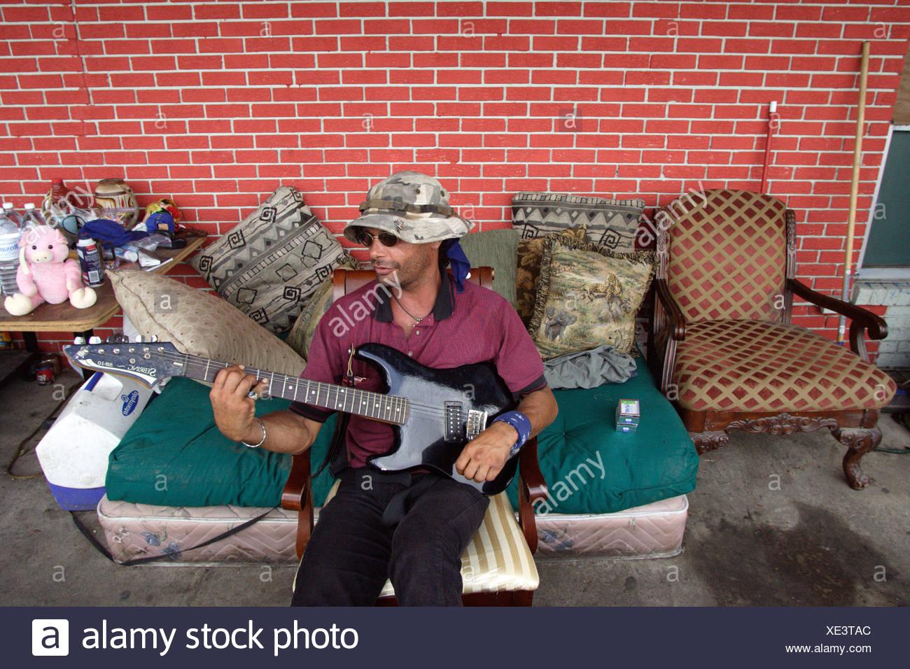 Man playing his electric guitar, after Hurricane Katrina - Stock Image