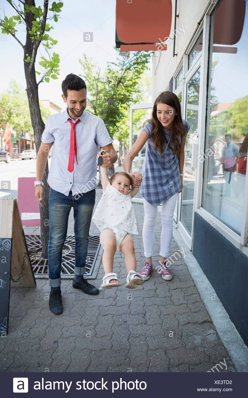 Parents swinging baby daughter on sidewalk - Stock Image