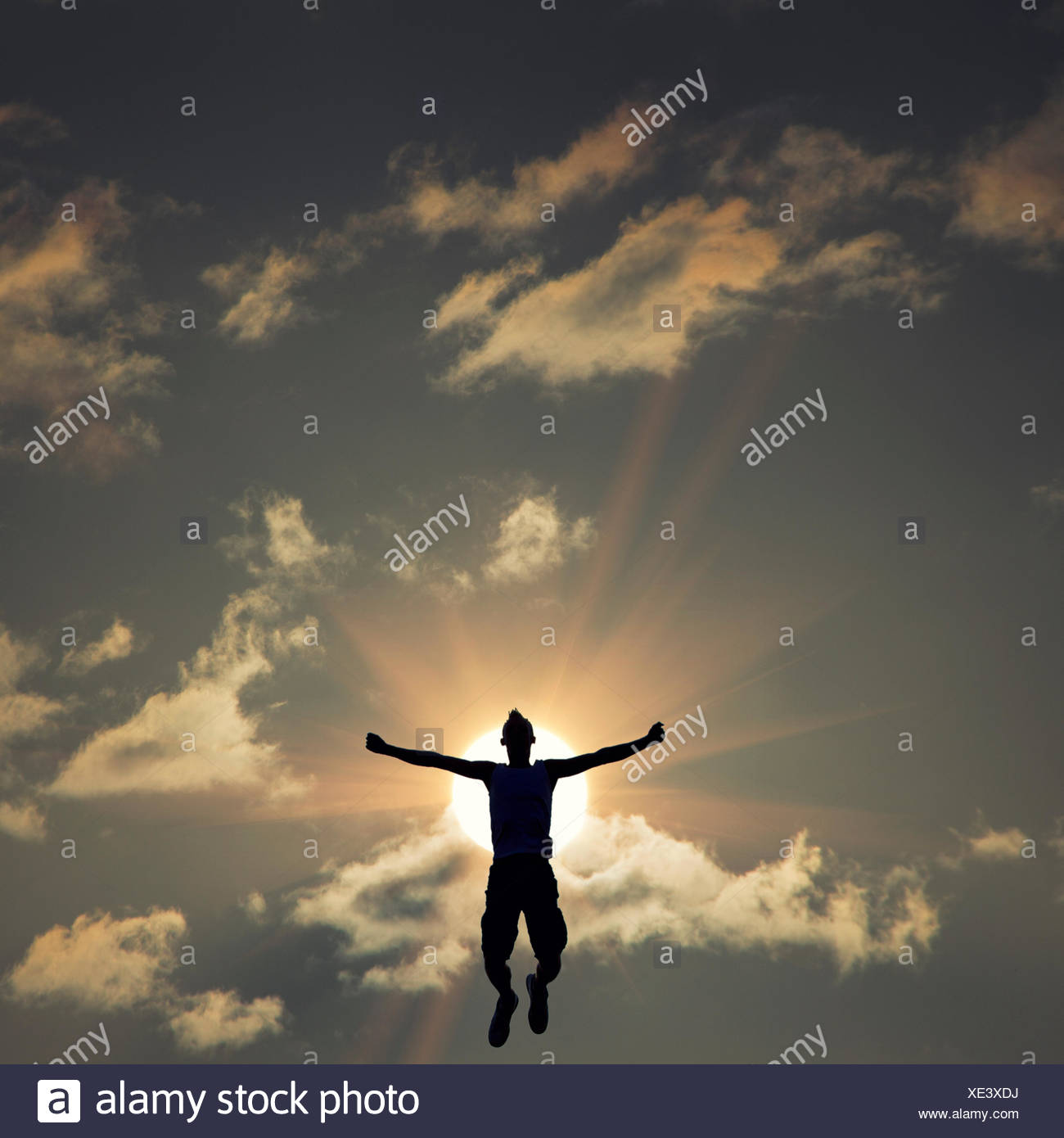 Silhouette of man jumping in front of the sun - Stock Image