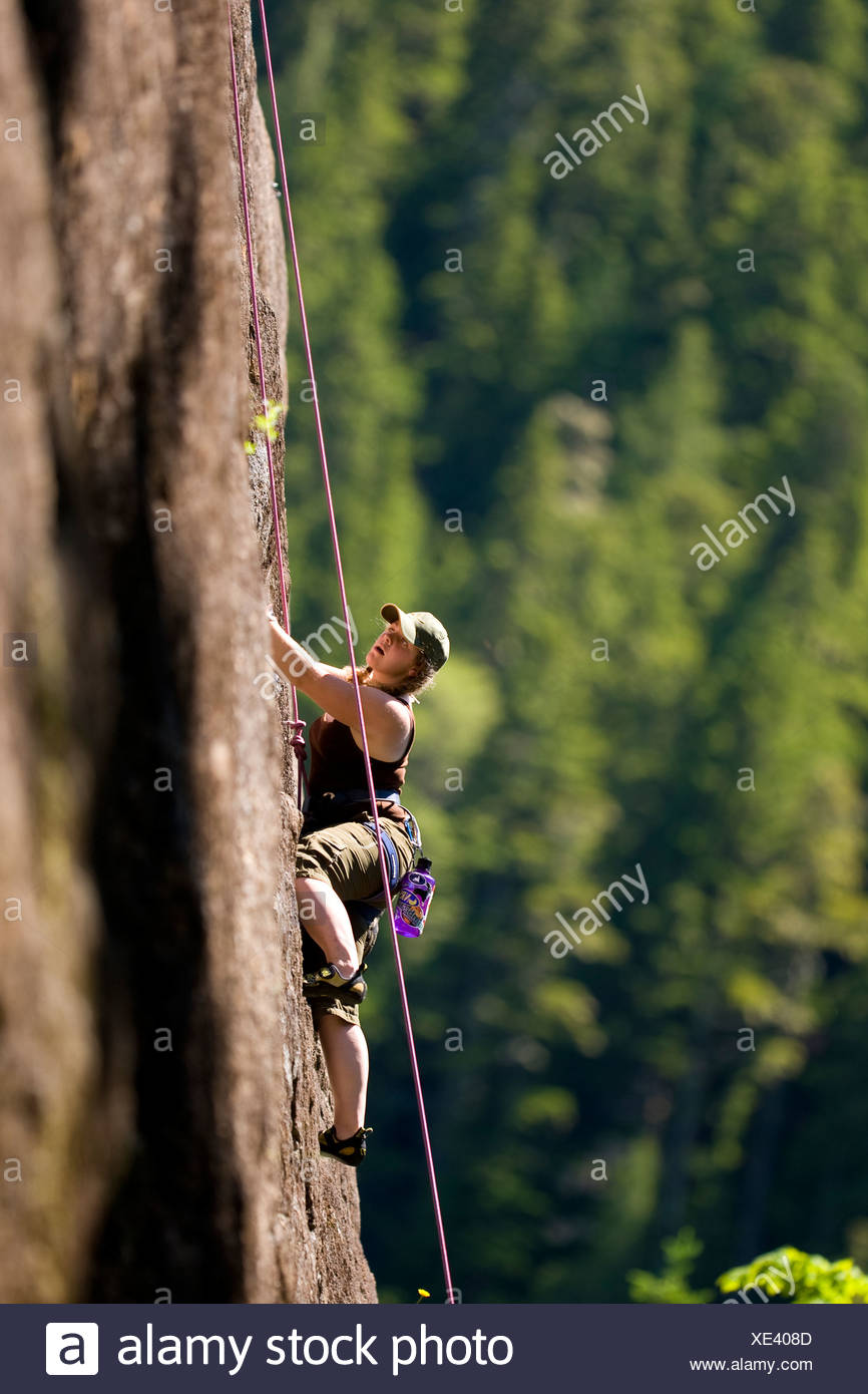 Female rock climber on Red Earth (5.9) Main Wall Crest Craigs in Strathcona Park.  Vancouver Island, British Columbia, Canada - Stock Image