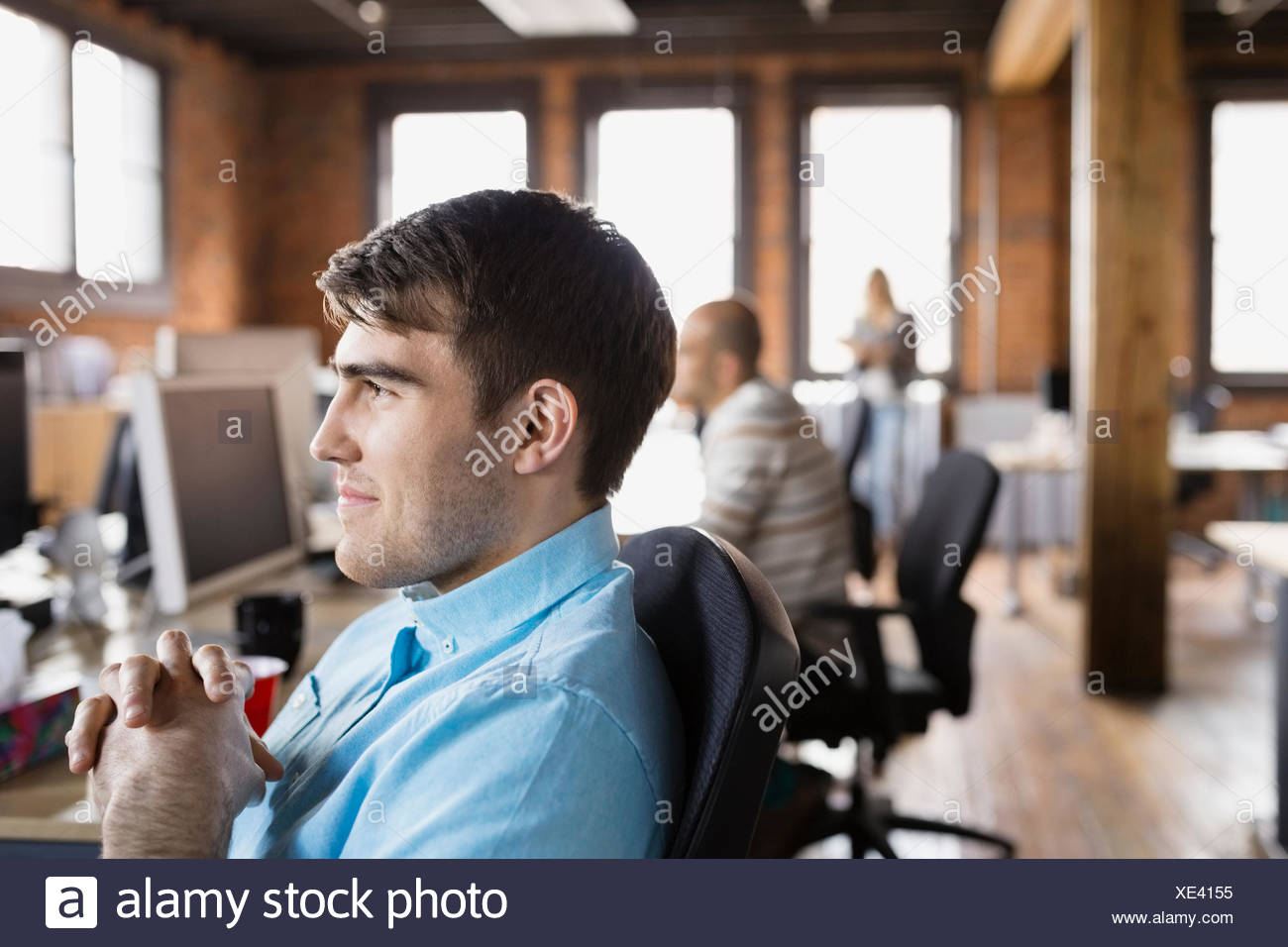 Pensive businessman looking away in office - Stock Image