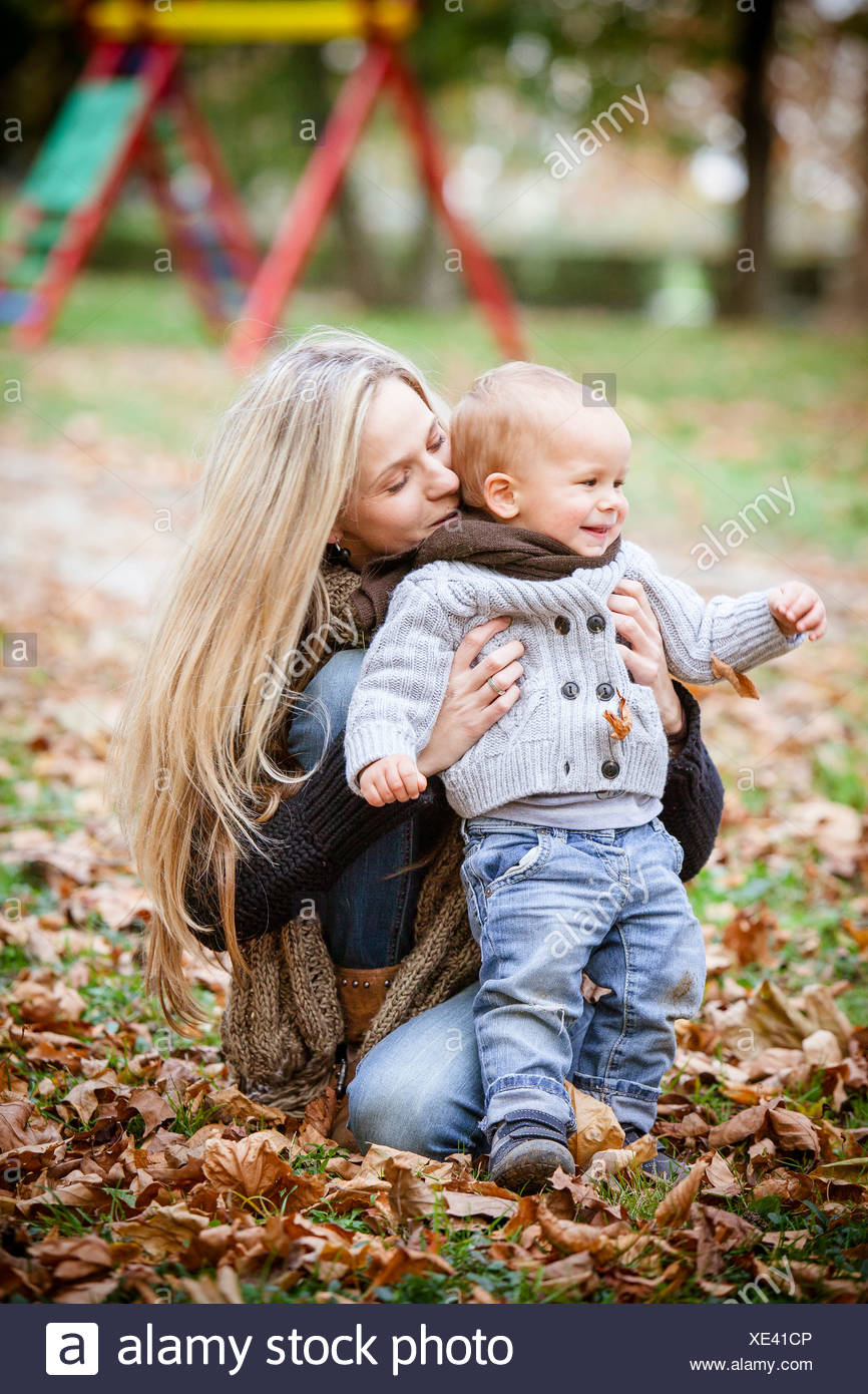 Mother and son playing with autumn leaves, Osijek, Croatia - Stock Image