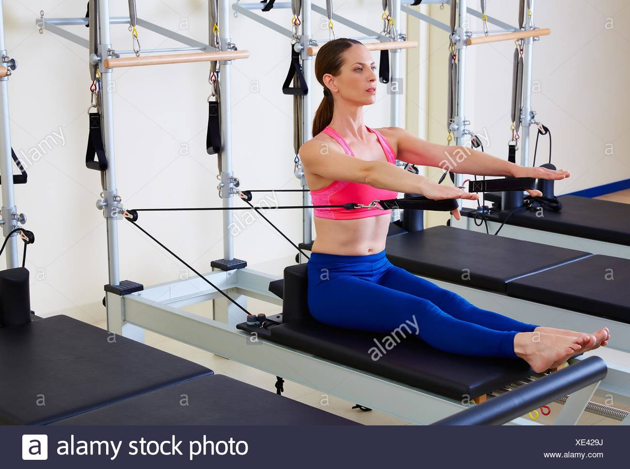 Pilates reformer woman stomach massage flat exercise workout at gym. - Stock Image