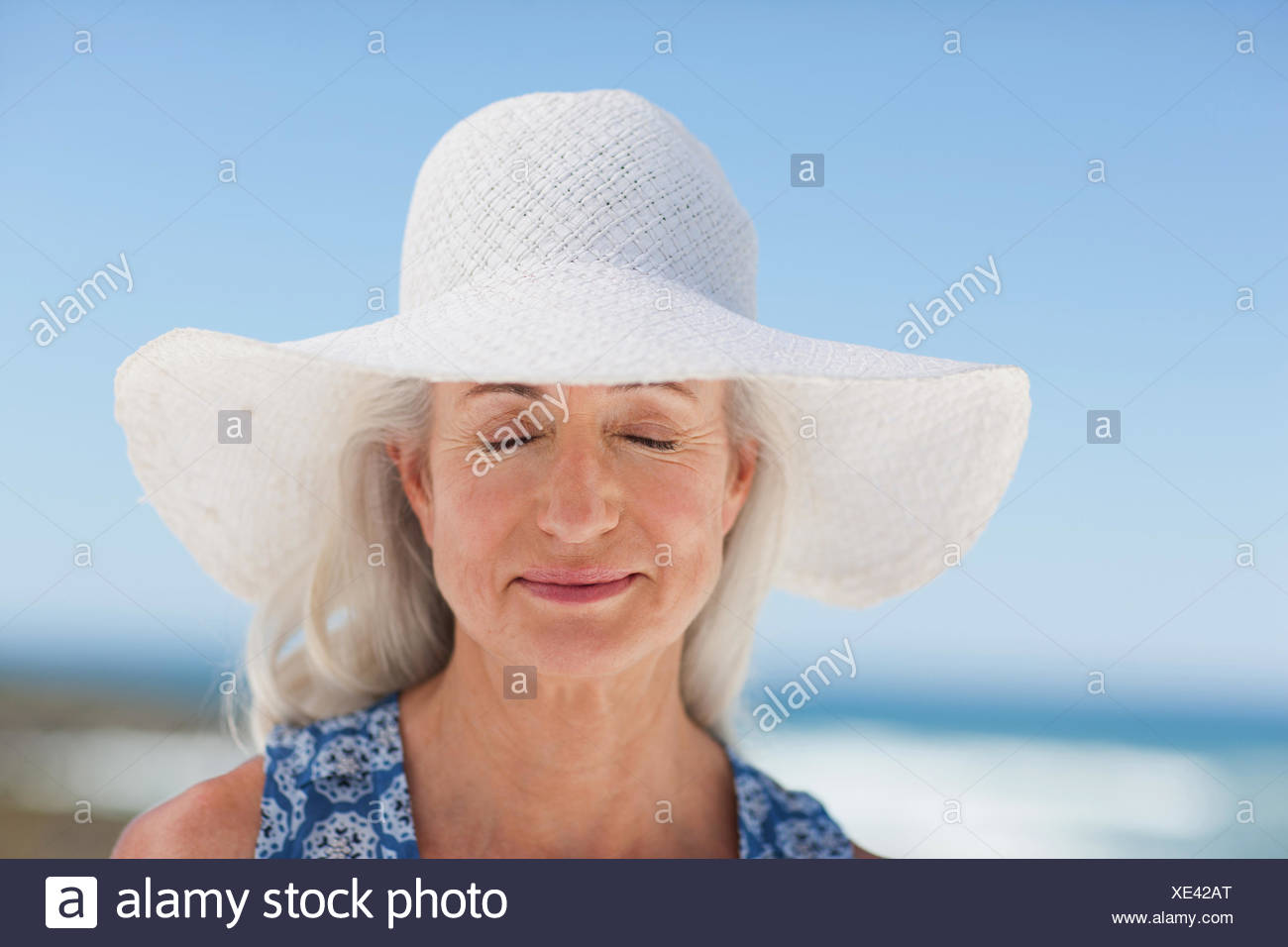 Close up of woman closing eyes with wearing sun hat - Stock Image