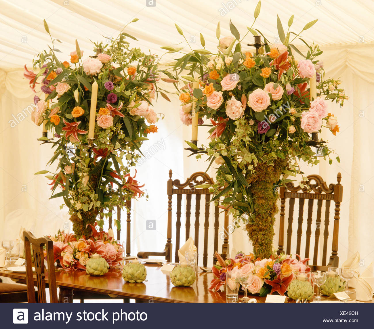 Pink Roses In Sumptuous Floral Arrangements On Table In Marquee