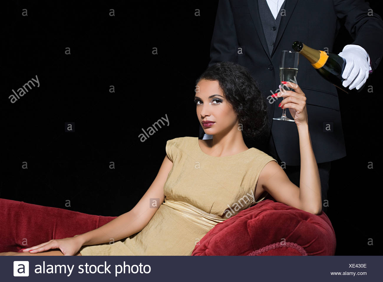 Woman having champagne served by servant - Stock Image