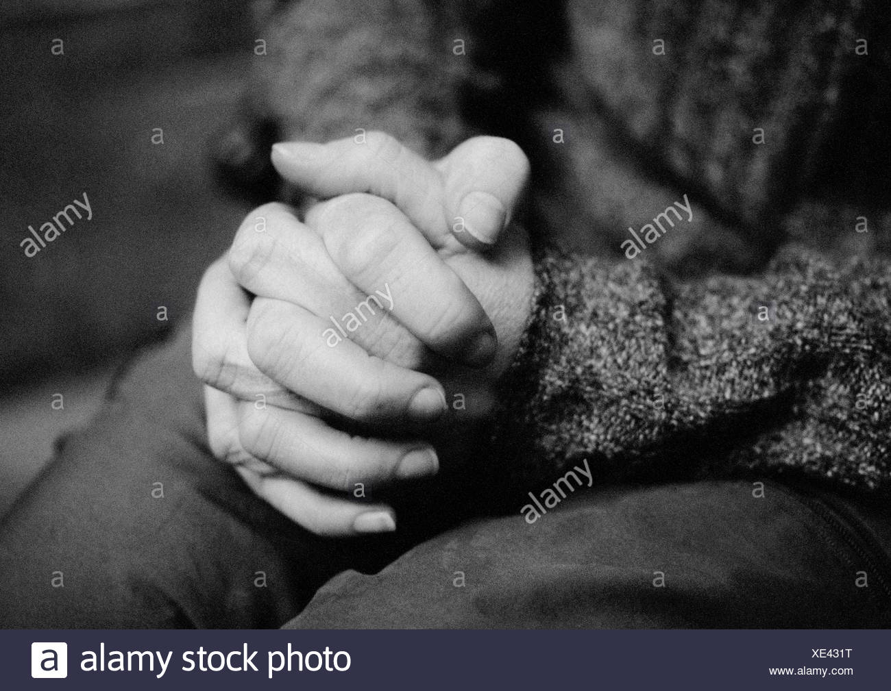 Clasped hands, close-up, b&w - Stock Image