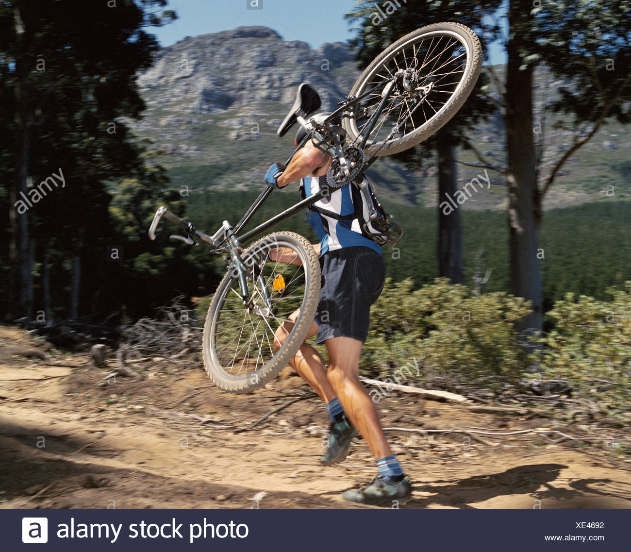 A man carrying a mountain bike on a path - Stock Image