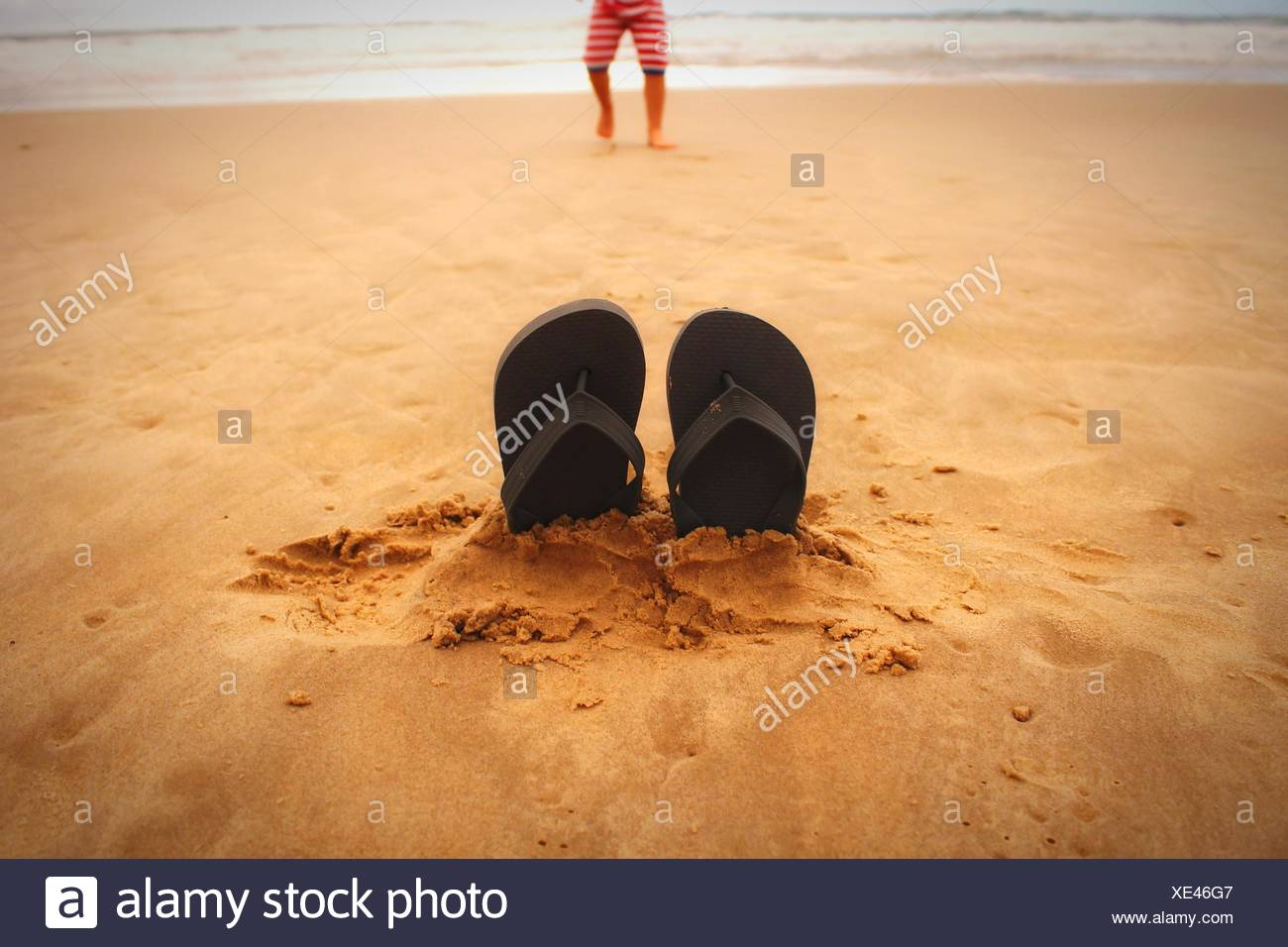 Close-Up Of Slippers On Sand At Beach - Stock Image