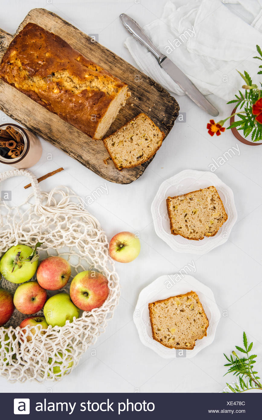 Cinnamon apple bread sliced on a wooden cutting board photographed from top view. Apples in a net bag and apple bread slices on two plates accompany. - Stock Image