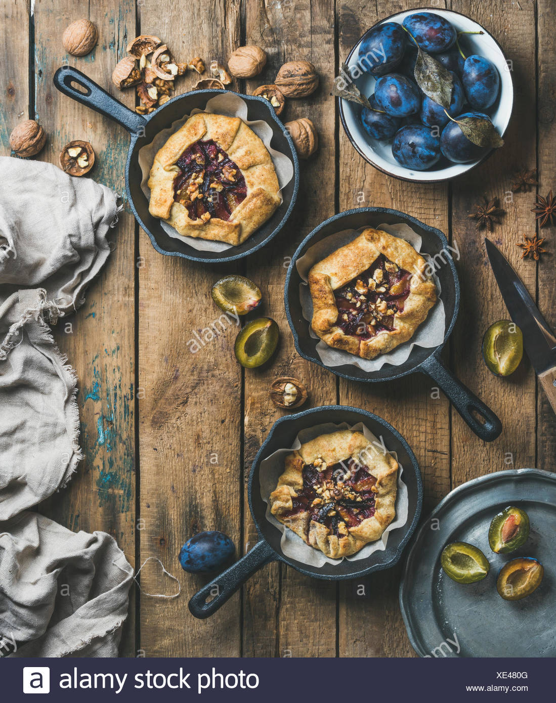Plum and walnut crostata pie with ice-cream scoops in individual cast iron pans over rustic wooden table, top view, copy space, vertical composition. - Stock Image