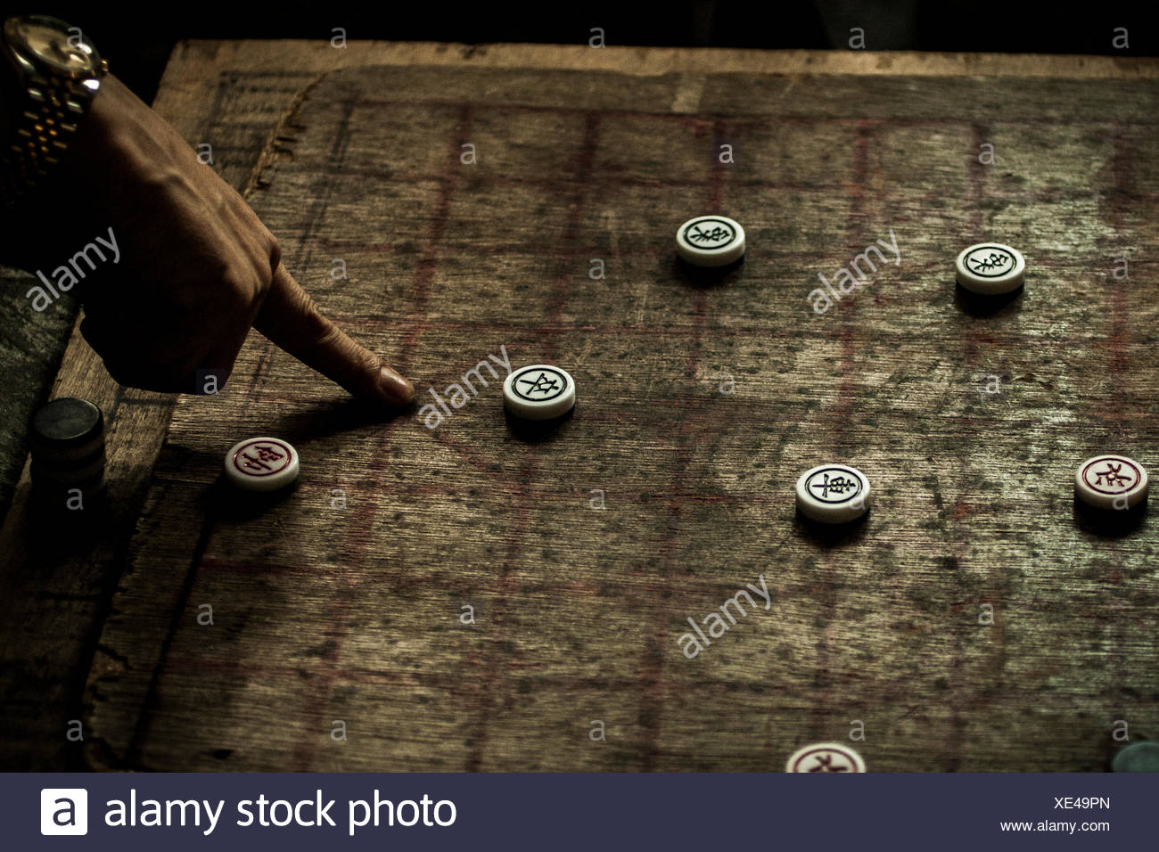 A man points to a strategic place on a Chinese chess board. - Stock Image