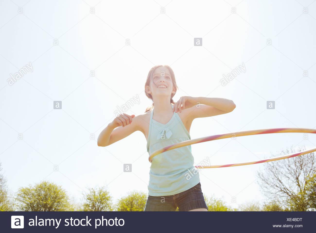 Girl playing with plastic hoop - Stock Image