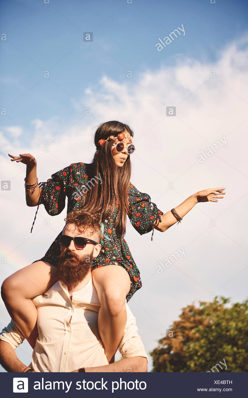 Young boho woman dancing on boyfriend's shoulders at festival - Stock Image