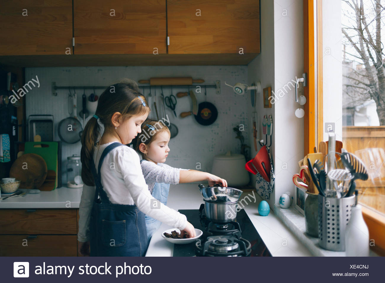 Girls melting chocolate in a kitchen - Stock Image