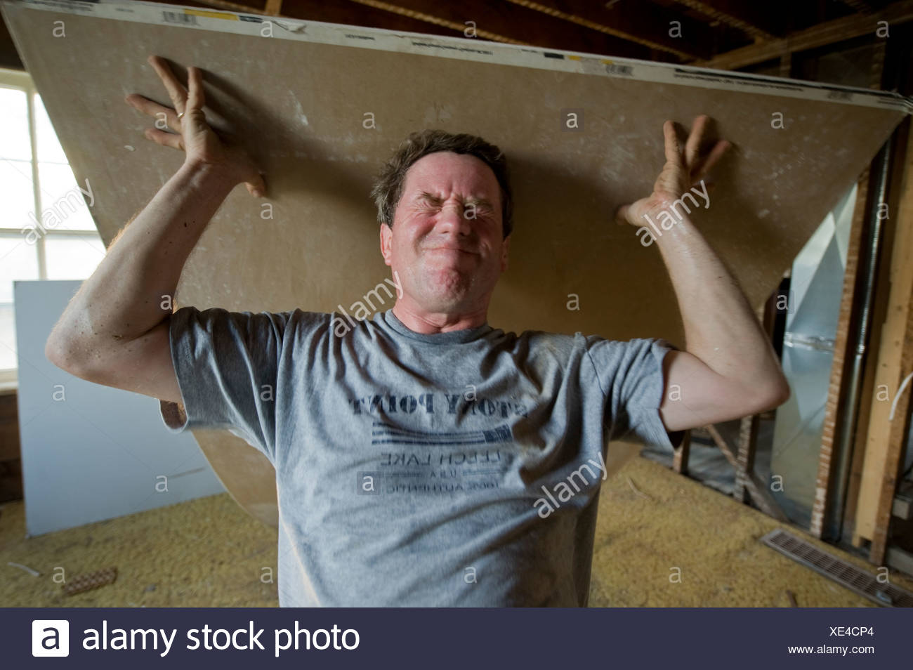 Weight maual labor sheetrock do it yourself projects home a man struggles to lift a piece of drywall stock image solutioingenieria Gallery