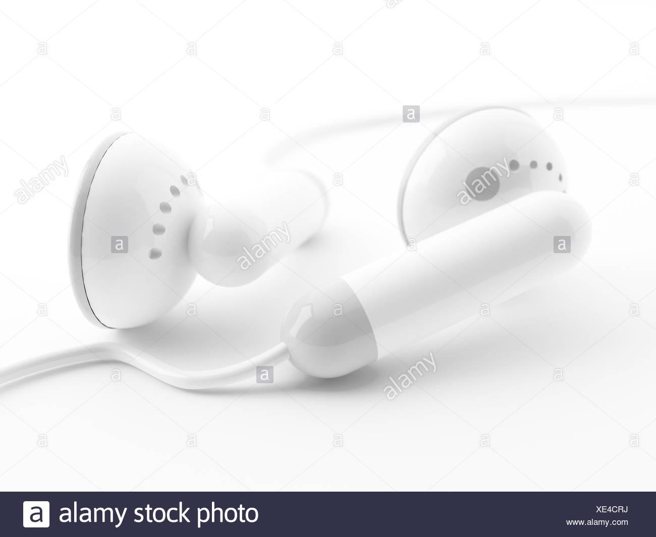 Modern light earphones on a white background - Stock Image