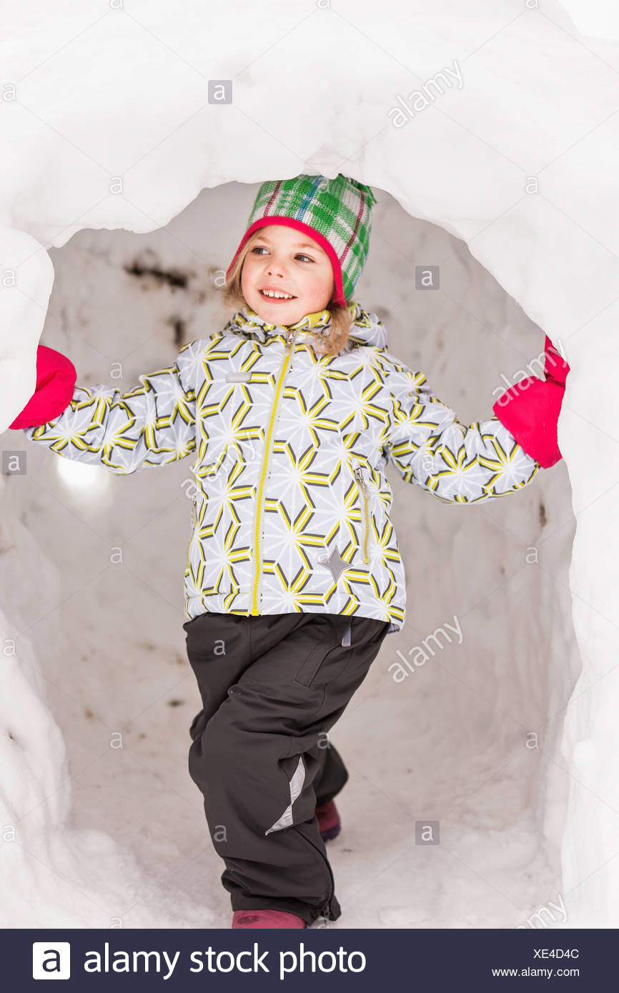 Girl wearing winter clothes standing in igloo - Stock Image