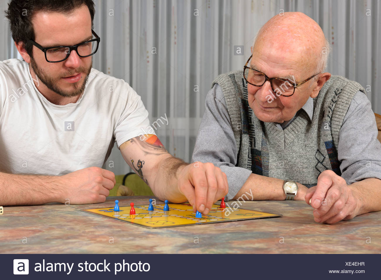 Grandfather and grandson playing together ludo at home Stock Photo