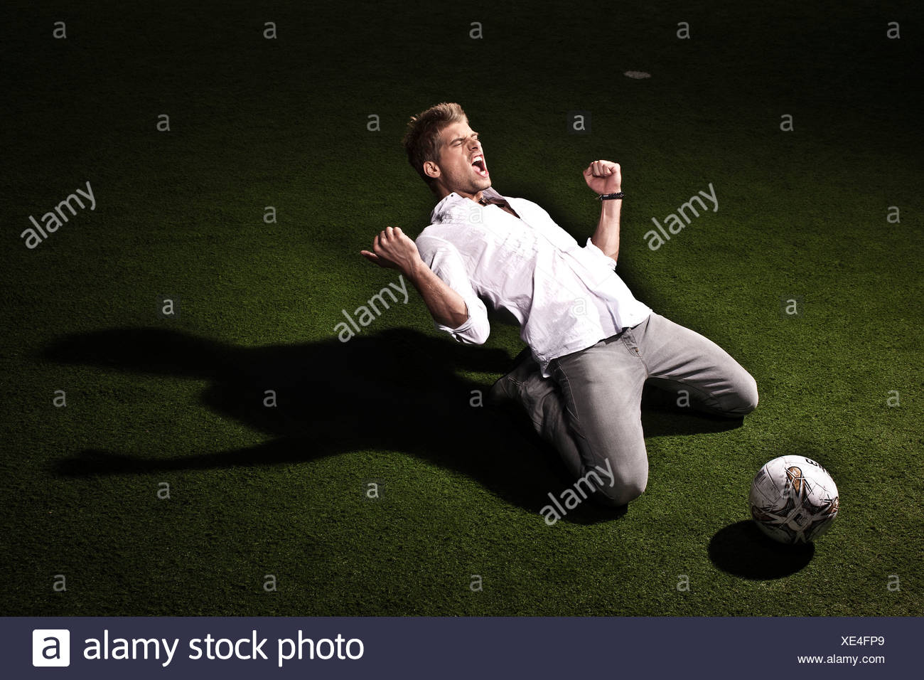 Footballer shouting and kneeling on pitch - Stock Image