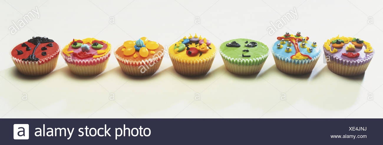 Seven Cupcakes Decorated With Colourful Icing And Sweets Side View