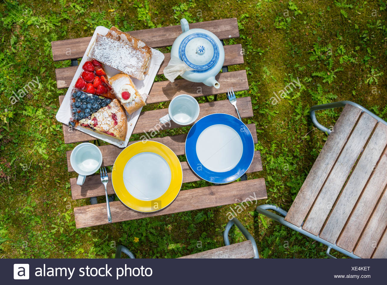 Laid garden table with cake and tea - Stock Image