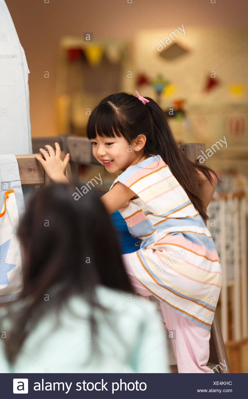 Cute girl playing on the bed - Stock Image
