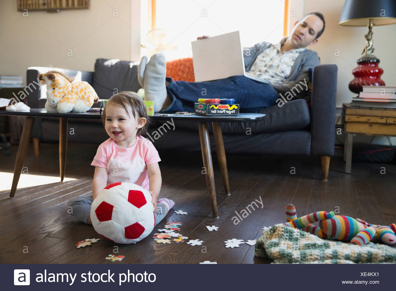 Father with laptop watching baby daughter play - Stock Image