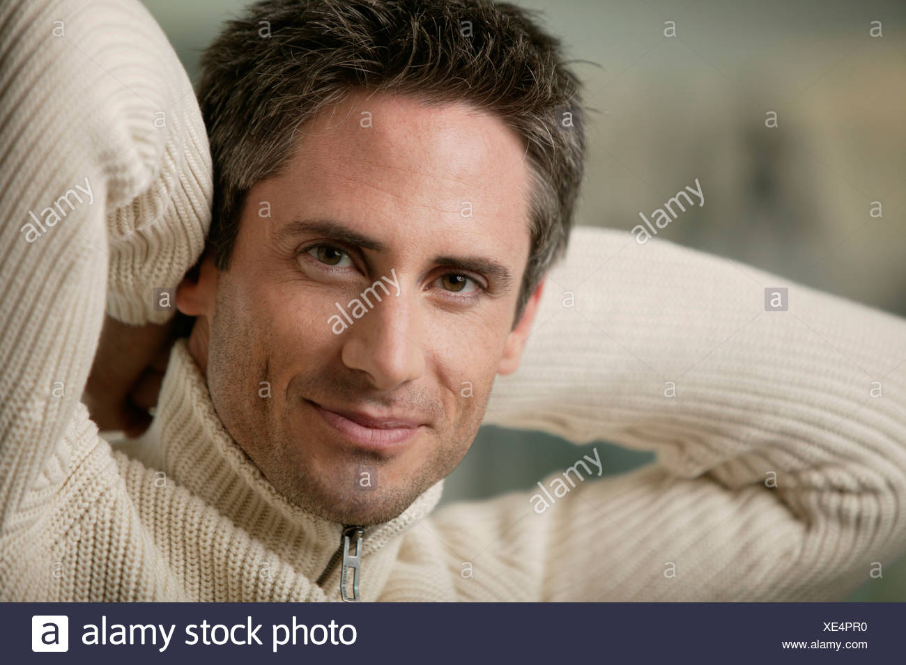 Man in light sweater looking relaxed - Stock Image