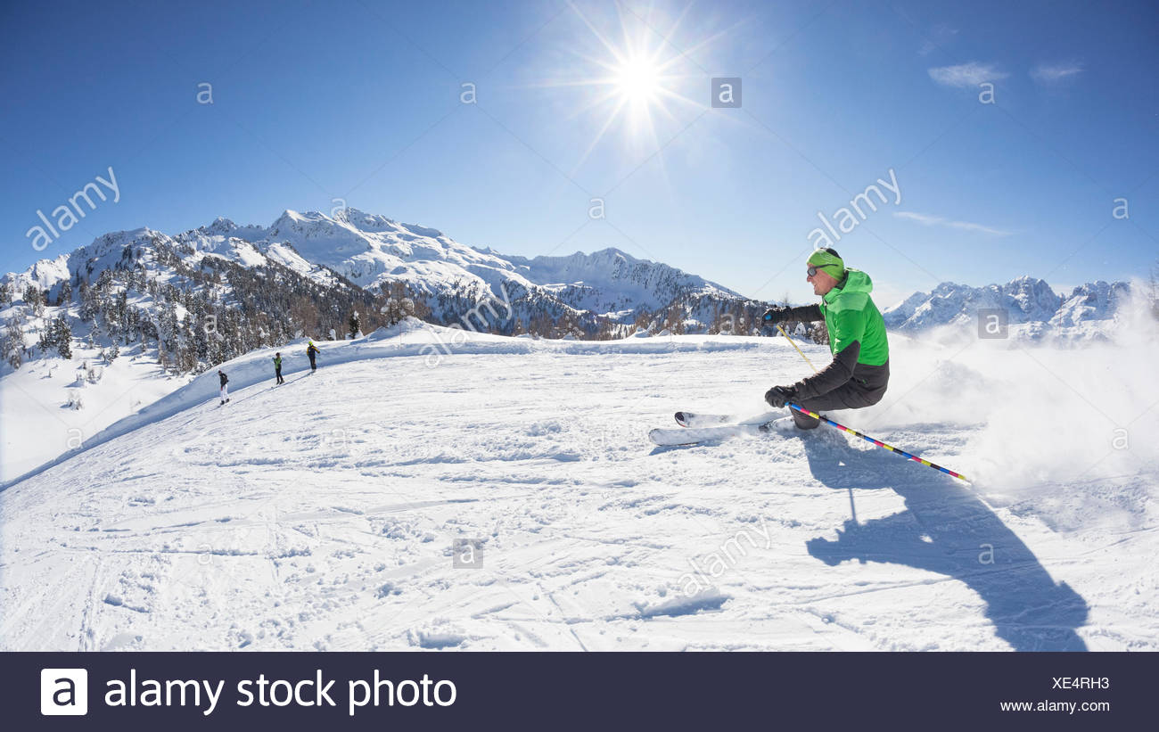 a skier is skiing along the slopes in the Folgarida ski resort with Brenta Group in the background, Trento province, Trentino Alto Adige, Italy, Europe - Stock Image