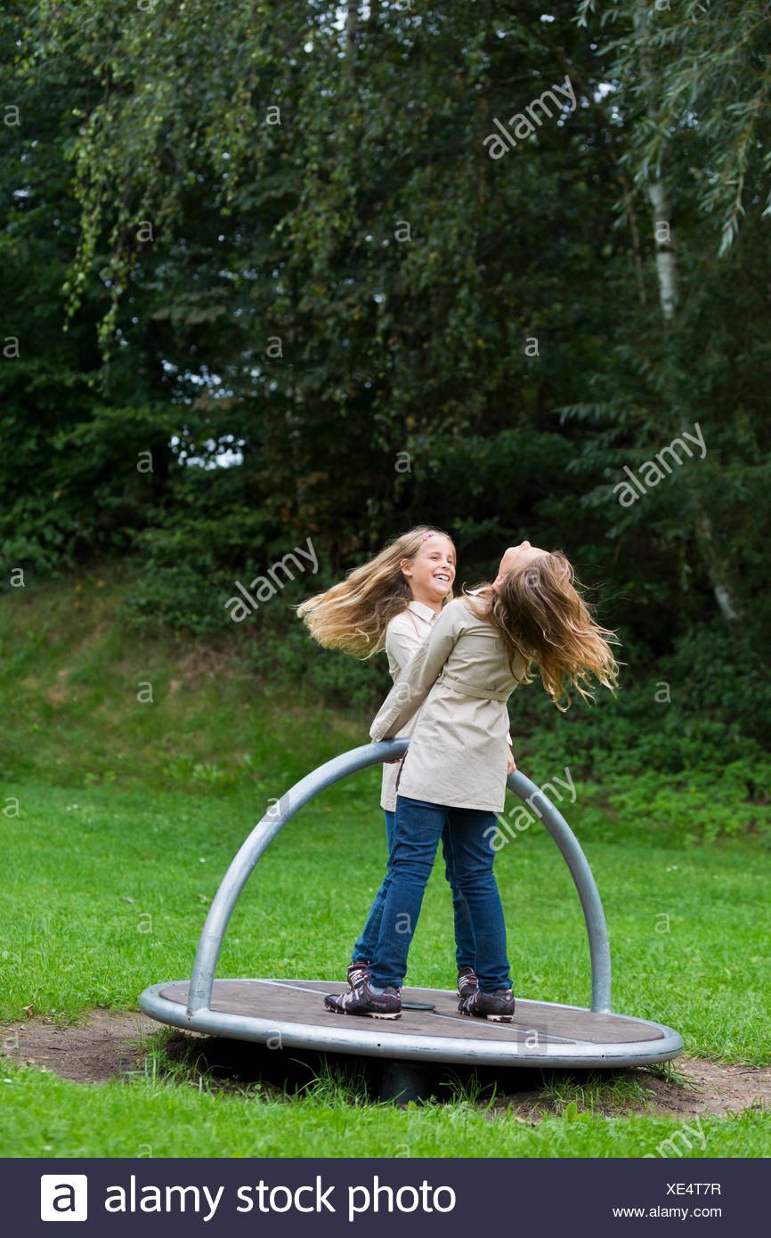 Twin girls, 9, turning on a carousel on a playground - Stock Image
