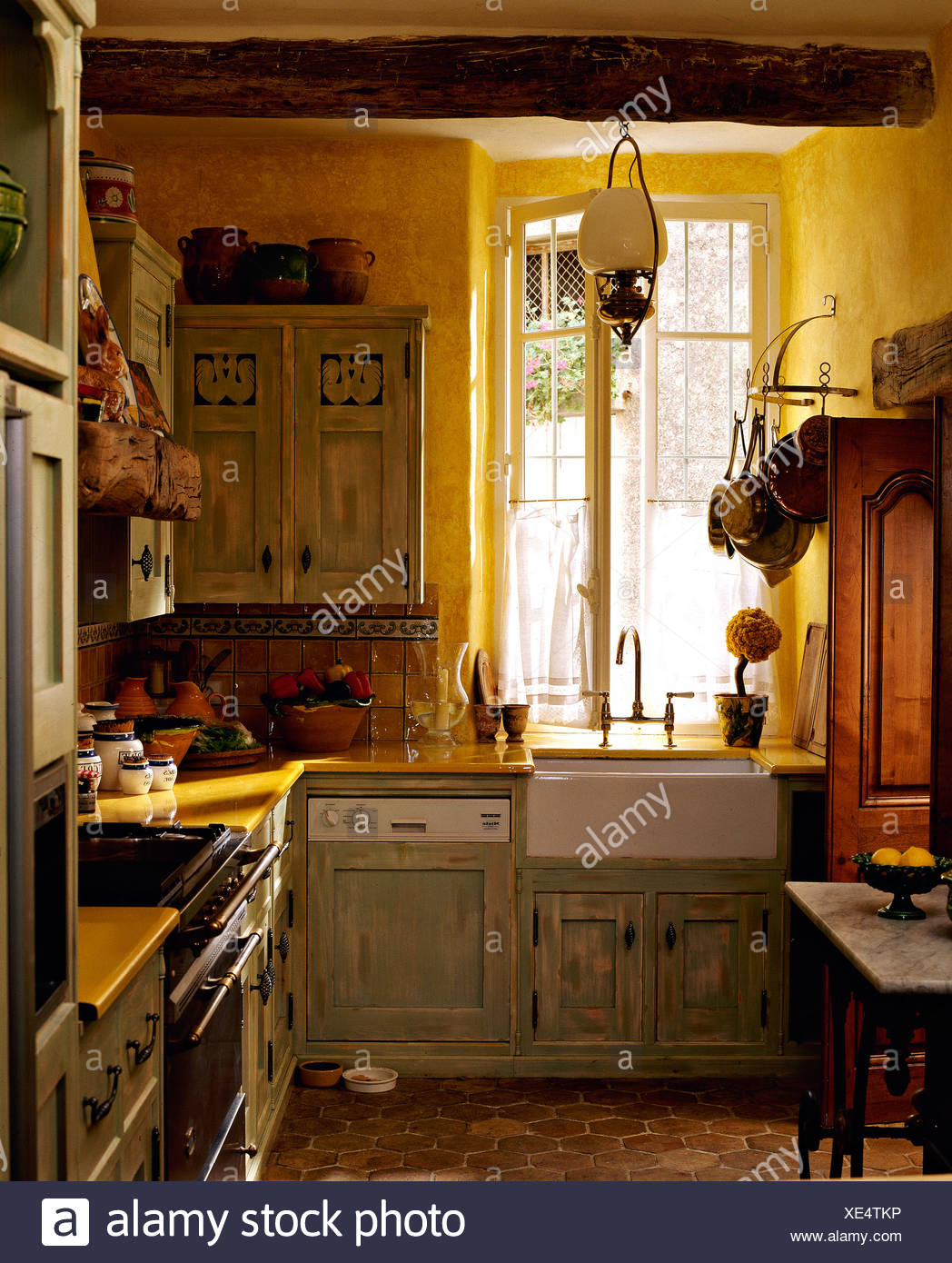 Pale Gray Green Distressed Cupboards In Yellow French Country Kitchen With Terracotta Tiled Floor And Belfast Sink Stock Photo Alamy