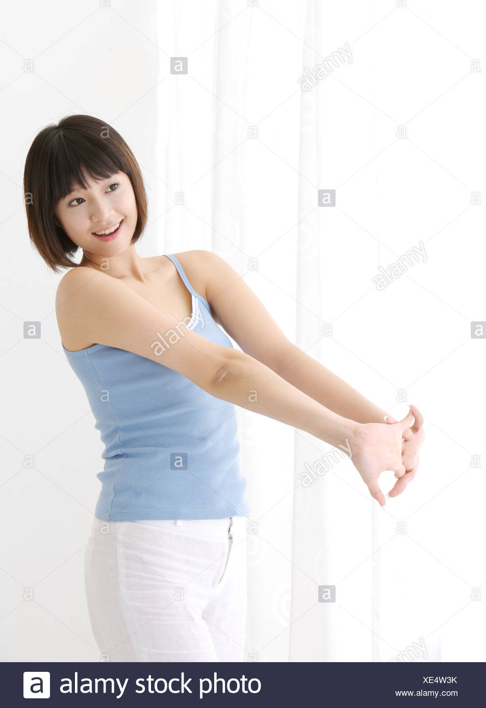 Young woman stretching arms in front of brast looking away