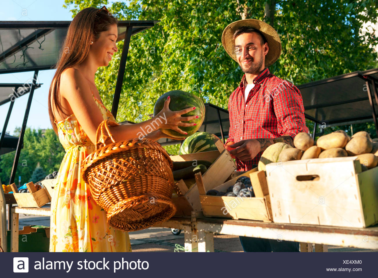 Young man selling fruit and vegetables at market stall - Stock Image