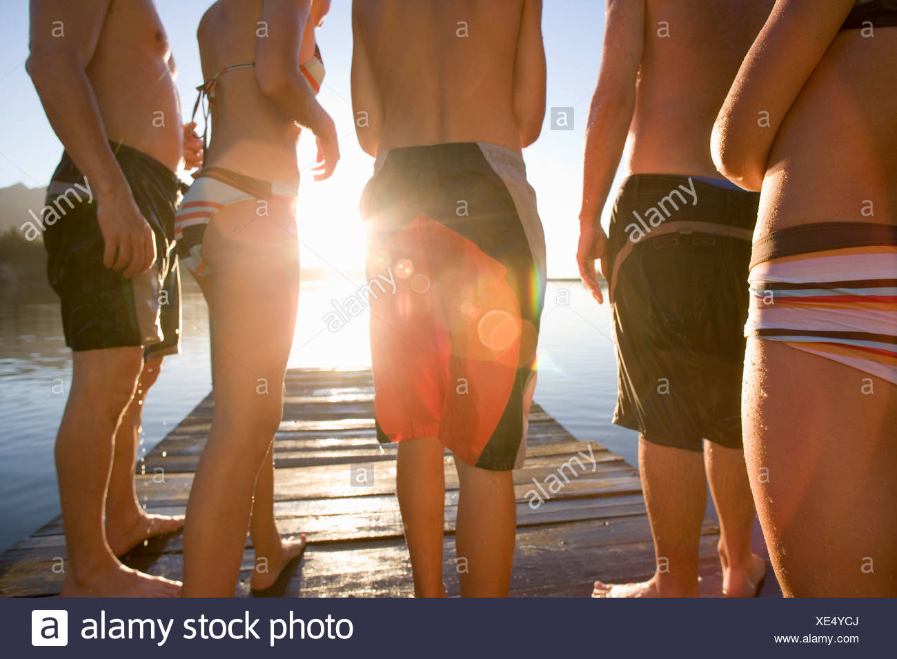 Five family members in swimwear standing on lake jetty at sunset mid section rear view lens flare backlit - Stock Image