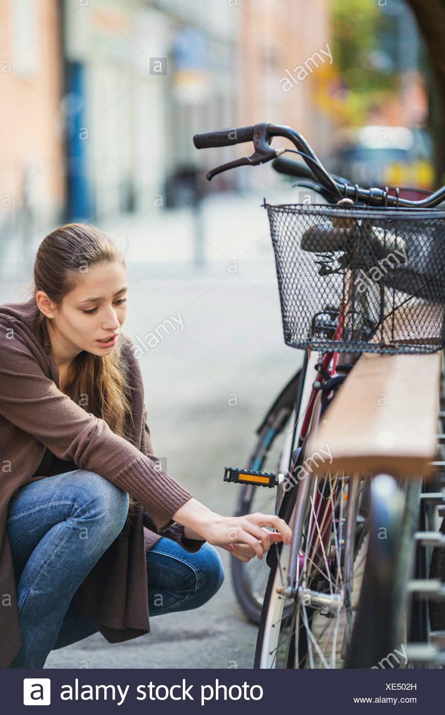 Young woman crouching while repairing bicycle - Stock Image