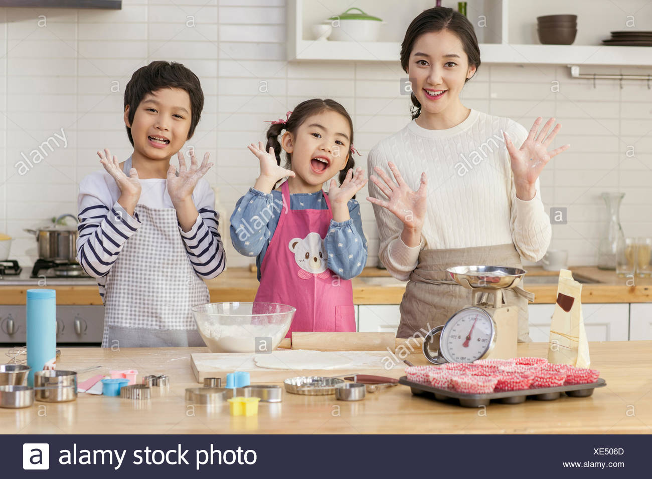 Smiling mother , daughter and son in same positions in kitchen - Stock Image