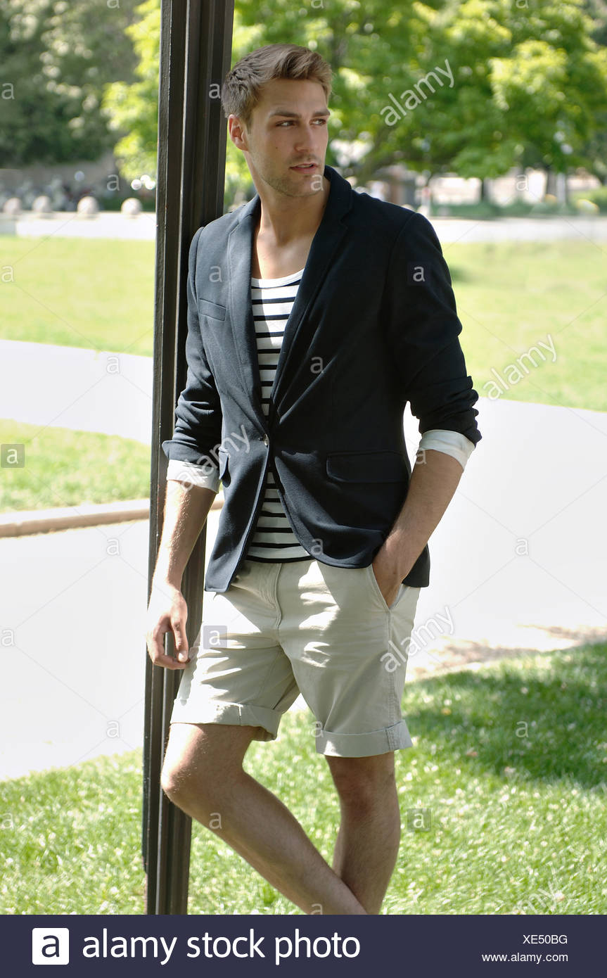 Young man in casual outfit leaning on a lamppost in a summerly park - Stock Image