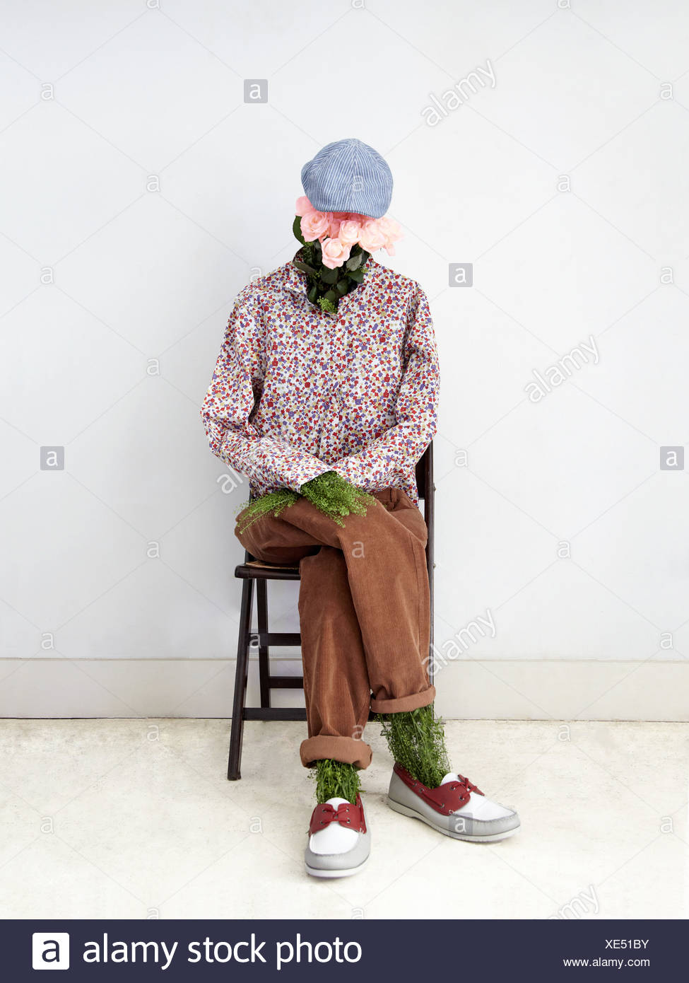Model of man made of plants sitting on chair - Stock Image