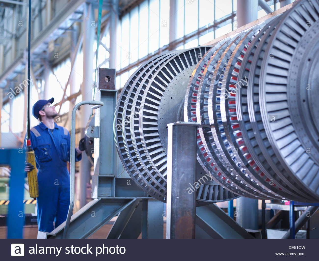Engineer lifting high pressure steam turbine with crane in workshop - Stock Image
