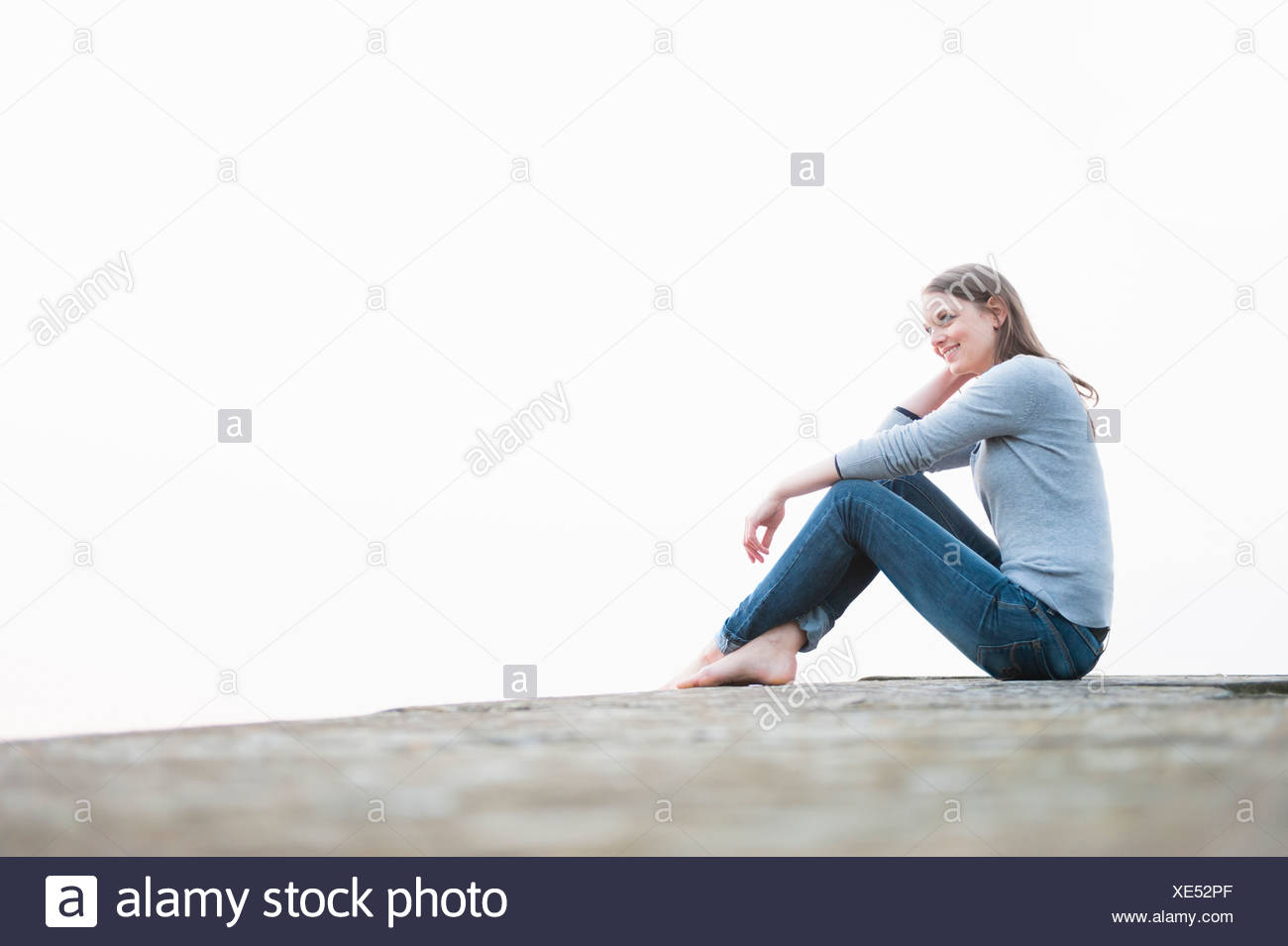 Contented young woman sitting on rock - Stock Image