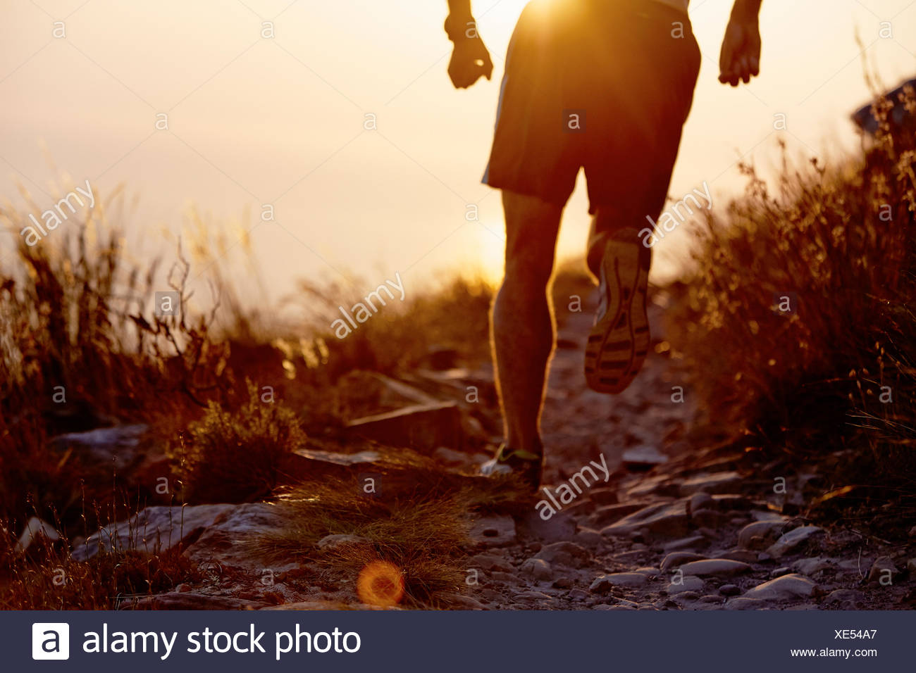 Man running on craggy trail at sunset - Stock Image