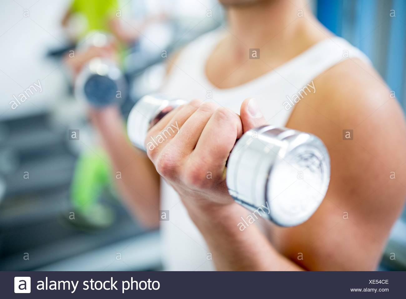 PROPERTY RELEASED. MODEL RELEASED. Young man holding dumbbells while work out, close-up. - Stock Image