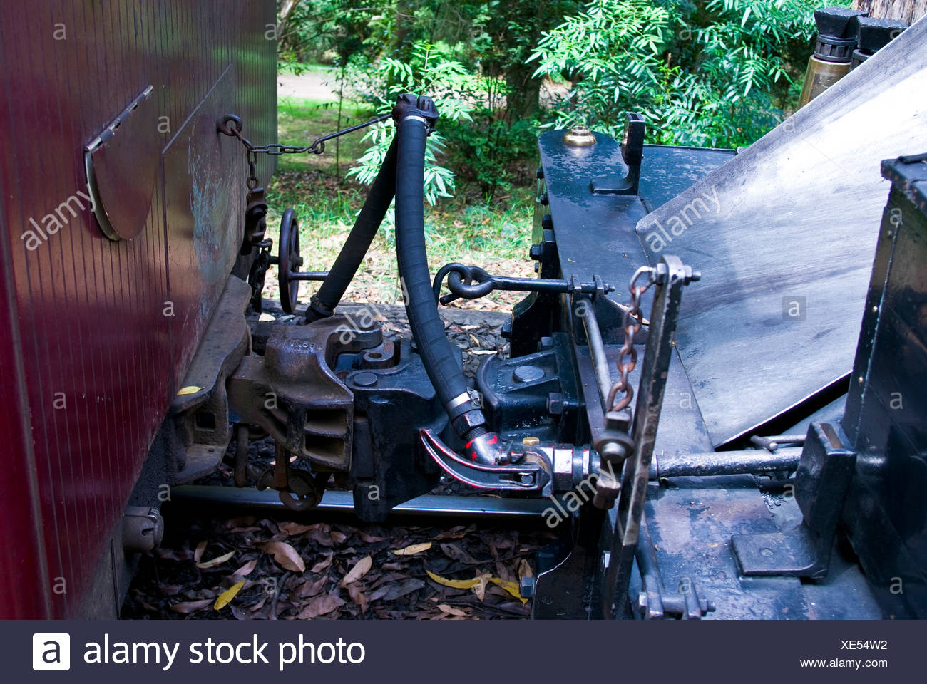 An antique steam engine locomotive coupled to a passenger carriage. - Stock Image